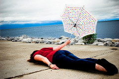 woman face down on concrete with inside out umbrella