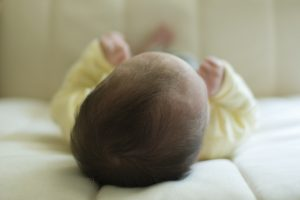 dark haired baby head lying down away from camera