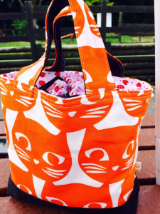 Medium sized cotton lunch bag in white material with orange cat print