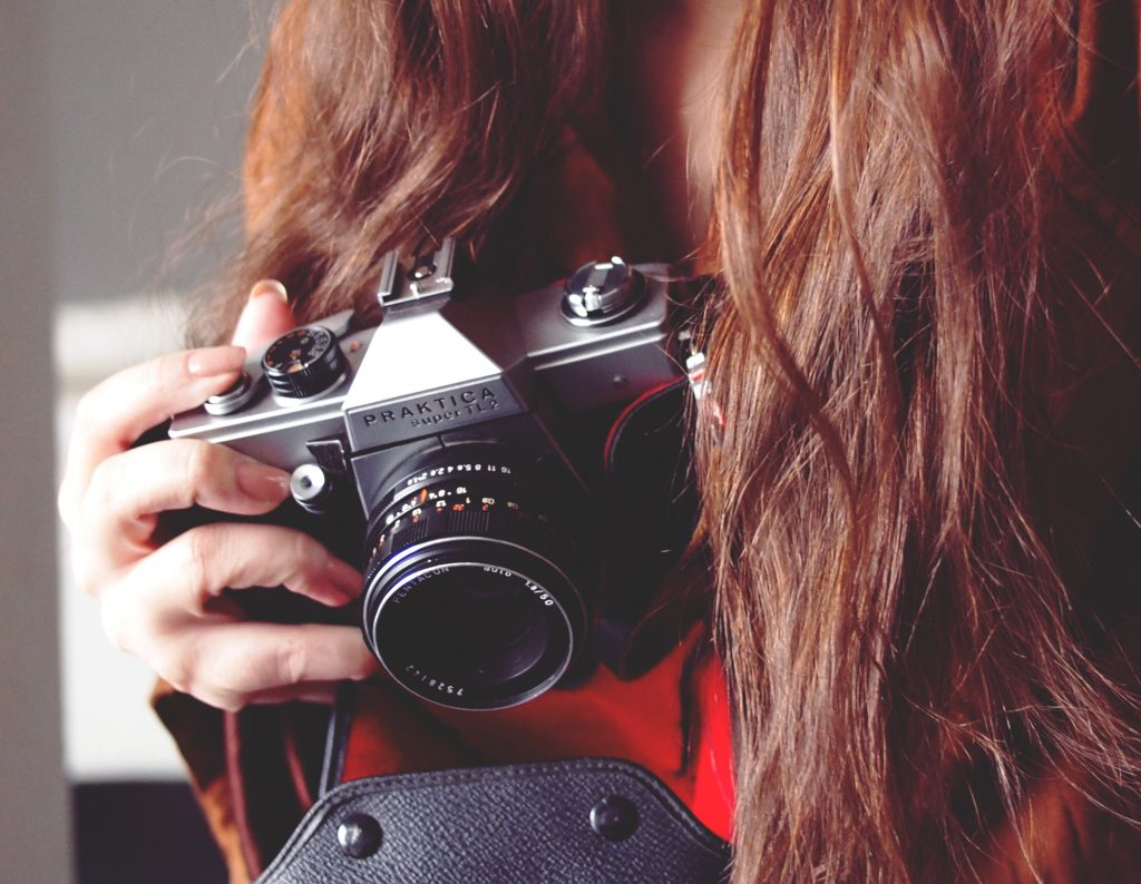woman with brown hair holding a camera