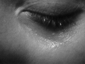 a closed eye with tears on a cheek
