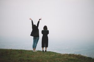 two women on a cliff edge looking out to see. one with folded arms and the other with arms in the air. dressed warmly in jeans and thick cardigans. grey sky, green grass foggy pale blue sea