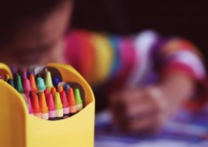 pack of crayons in the front a child colouring and blurred in the back