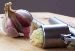 A bulb of garlic with cloves missing and crushed garlic coming out of a press all on a chopping board
