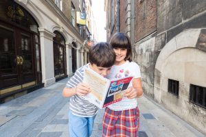 Little girl and boy on a cobbled street looking at a map
