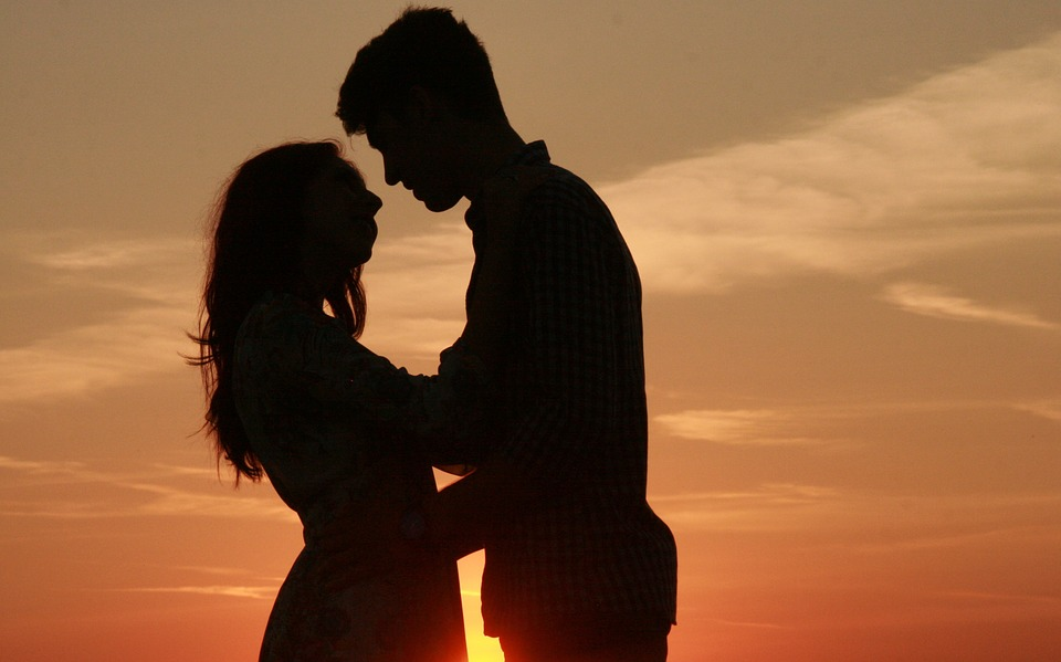 a couple in shadow with the sunset behind them about to kiss