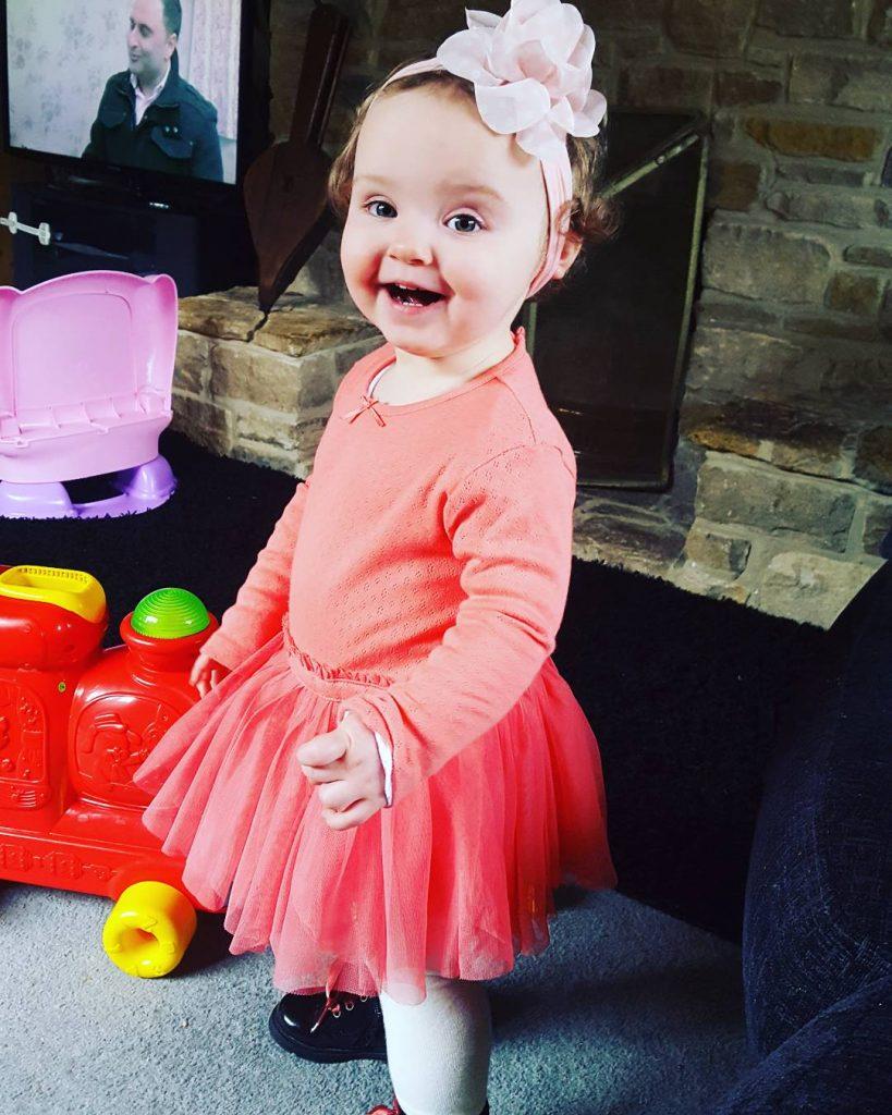 Alyssa in a peach tutu and peach flower head band smiling