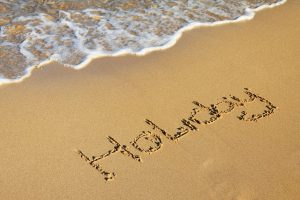 sea coming up the sand with the word holiday written on the sand