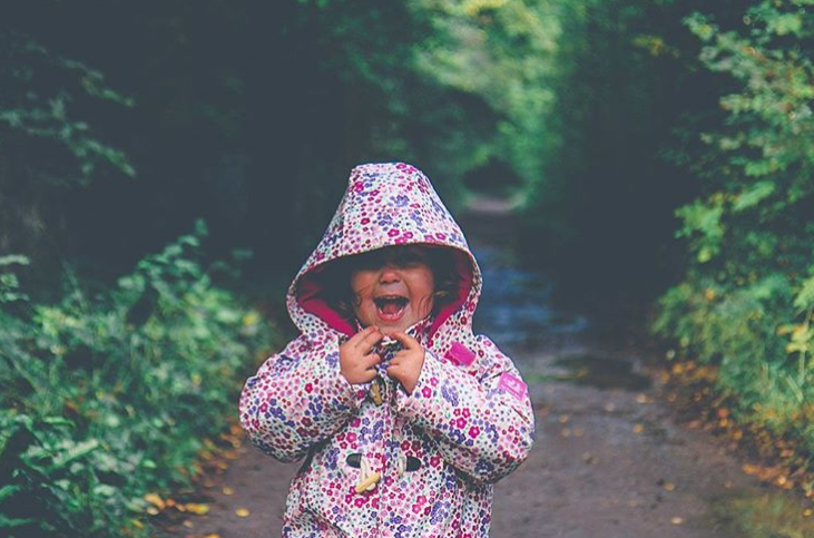 little girl on a path surrounded by green leaves wearing a pink purple and white floral rain mac and laughing at the camera