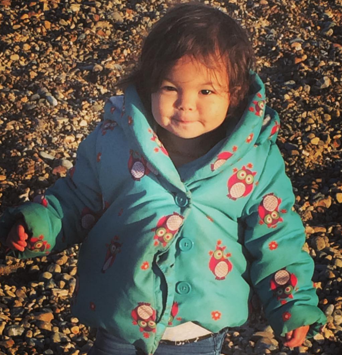 little girl standing on a pebble beach with dark brown curly hair and a blue coat on