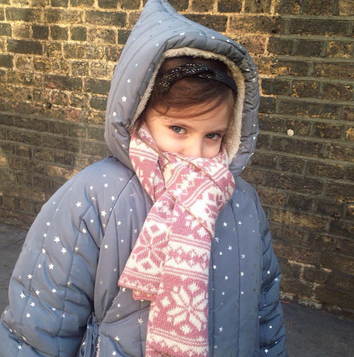 little girl in a grey coat with silver stars in it and a pick and white scarf covering half her face in front of a brick wall