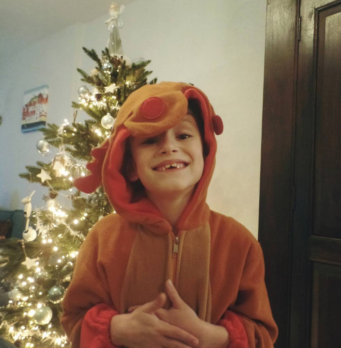 little boy smiling in front of a tree wearing a rudolph onesie