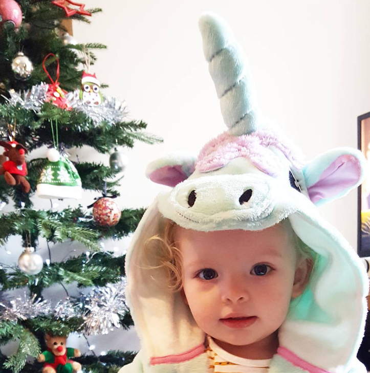 little blonde girl in front of a christmas tree in a unicorn dressing gown