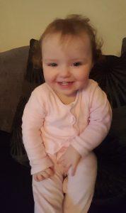 alyssa on black sofa in pink babygro