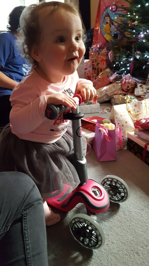 alyssa on her new pink scooter with a big smile and presents behind her