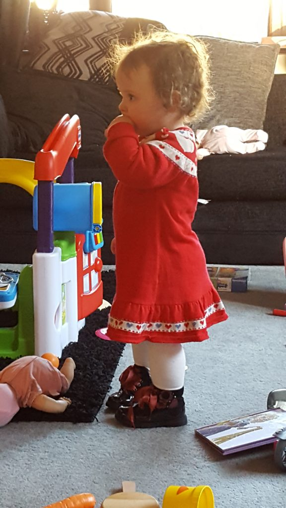 Alyssa stood sucking her finger wearing a red dress with a gingerbread trim with white tights and black boots surrounded by toys