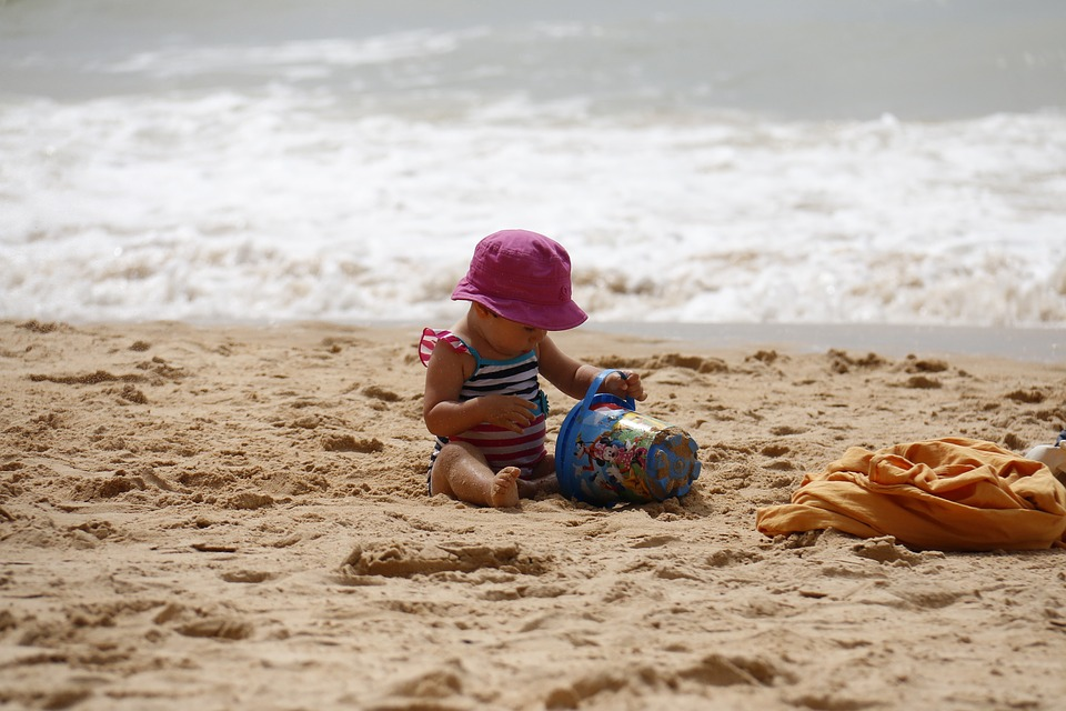 little girl playing on the beach with a bucket in the sand and the sea behind  her