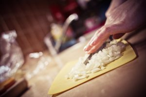 slicing onions on a chopping board in a kitchen