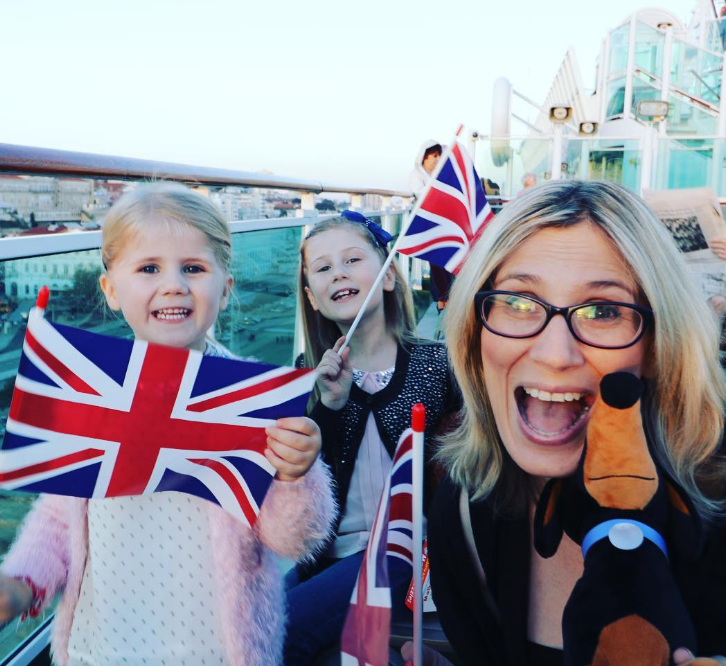 woman holding a sausage dog cuddly toy and two little girls holding Union Jack flags smiling at the camera on top of an open air bus