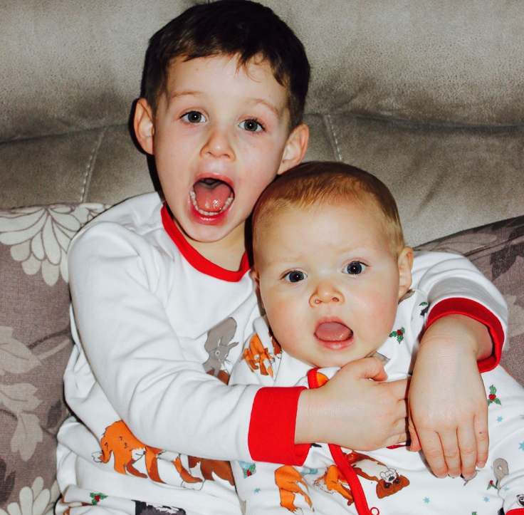 two children one big one small in matching pyjamas with their mouths open at the camera
