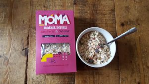 a purple box of MOMA cereal with a bowlful next to it and a spoon