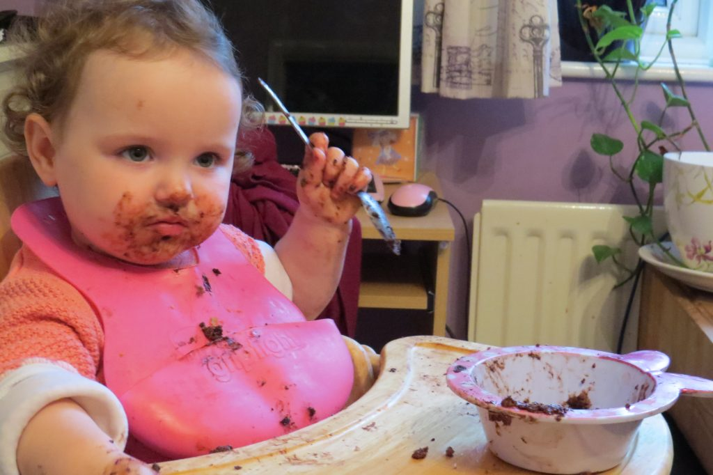 alyssa in a highchair holding a spoon with a pink bib on and the tray bowl and her face covered in chocolate cake