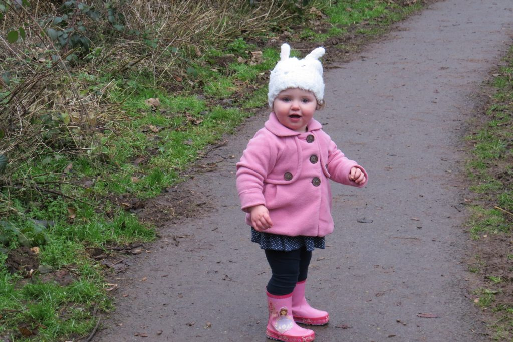alyssa on a path surrounded by trees in a pink coat and wellies, a white bunny hat and blue jeans smiling at the camera