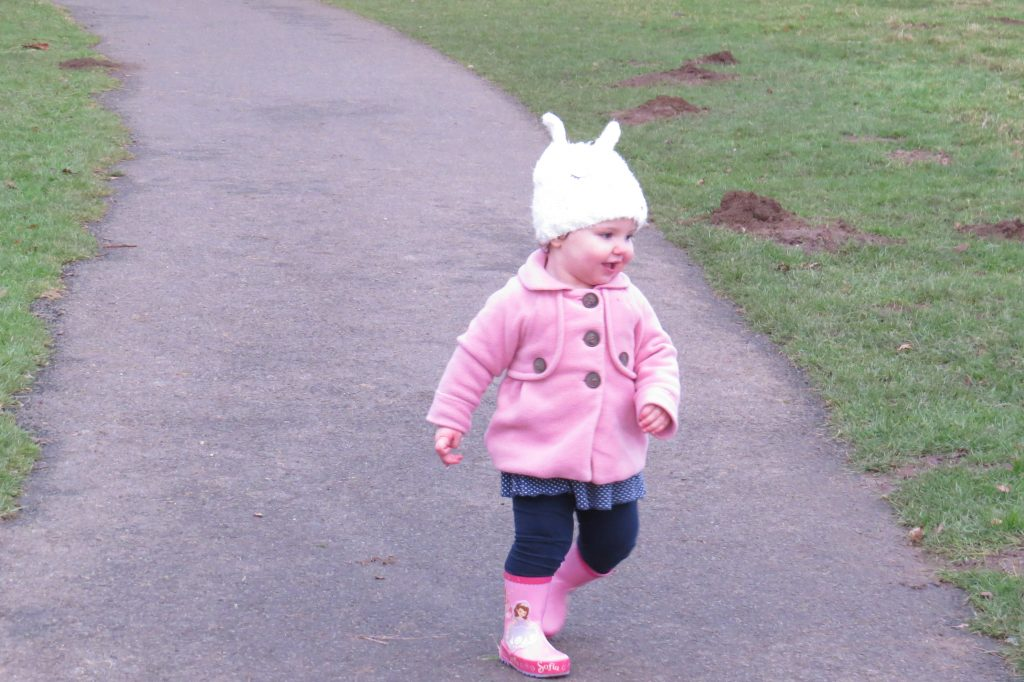 alyssa running and laughing down a path wearing a white bunny hat a pink coat and wellies and blue jeans