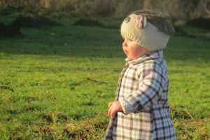 alyssa in a plaid brown and pink coat with a wollen panda headband on some grass with the sun shining down