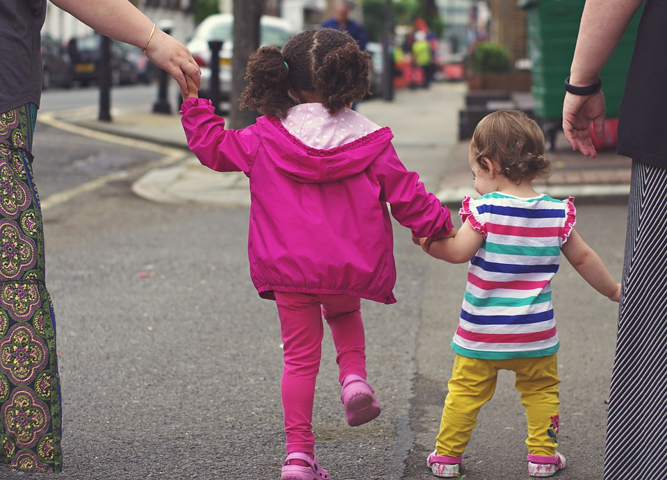 two little girls holding hands and an adult either side holding hands crossing road together