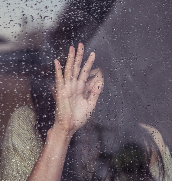 woman looking out of a window covered in rain with her hand against the window