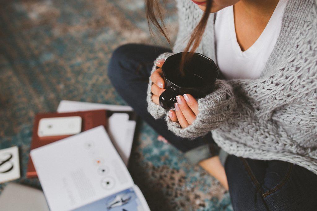 woman sat in a woolen cardigan cupping a mug of coffee sitting cross legged reading a book