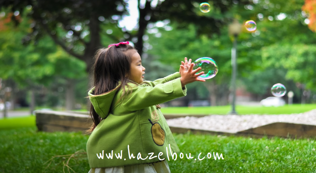 little girl in a green coat catching a bubble outside on some grass