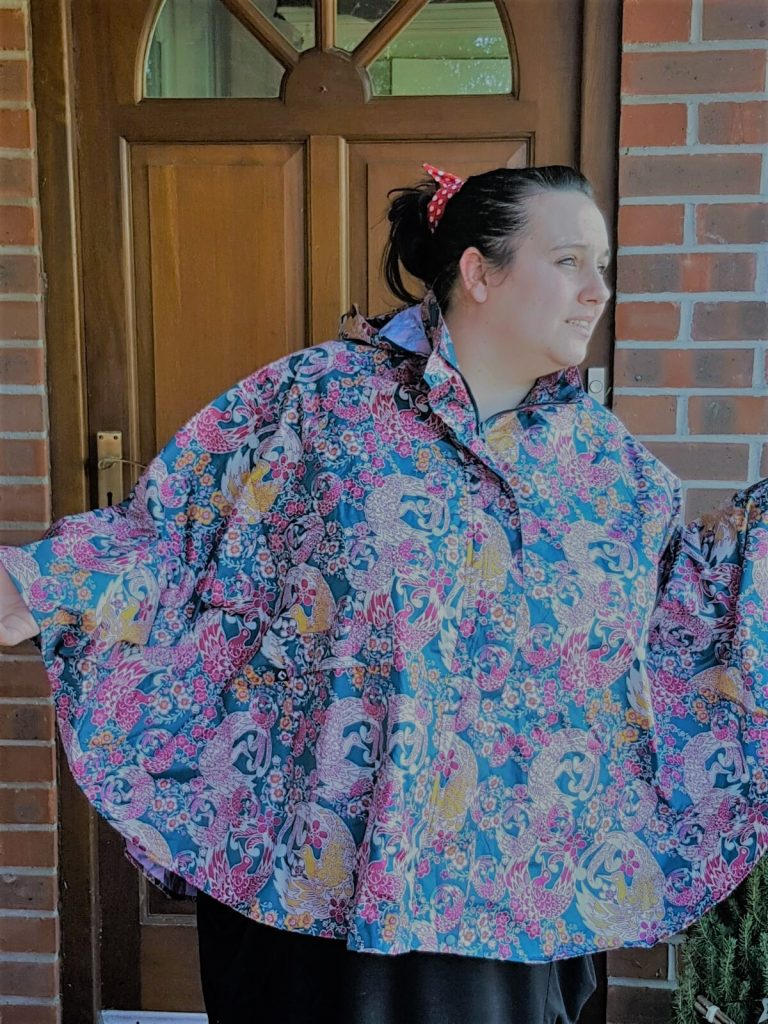 me in a rain poncho with a blue yellow and purple oriental bird pattern hands up looking for rain