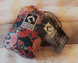 blue pink white and yellow oriental bird patterned bag with the November Rain black and white logo on it on a white wooden floor