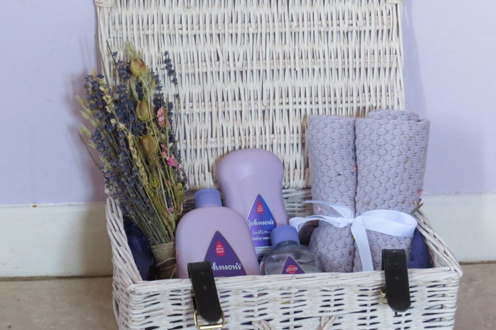 a white wicker hamper open with some dried flowers in a purple blacket tied with a white bow and 3 purple bottles of baby bath products - bubbles, wash and massage oil