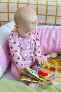 baby sat reading a book