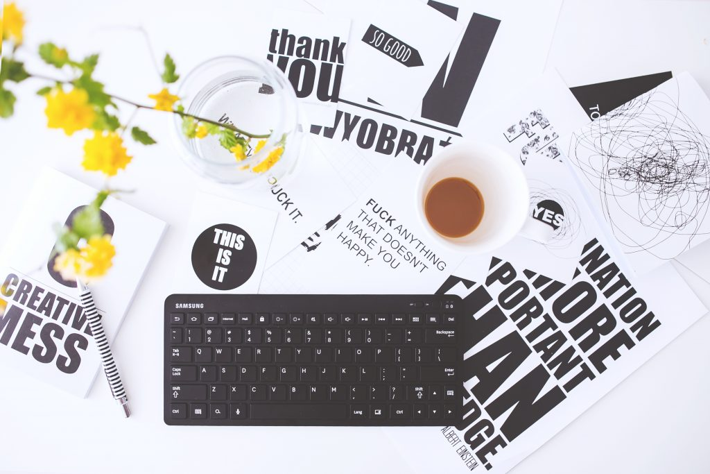 a keyboard on a white table covered in pieces of paper with bold print text all over them, a mug of coffee and a glass with a single stem of yellow flowers