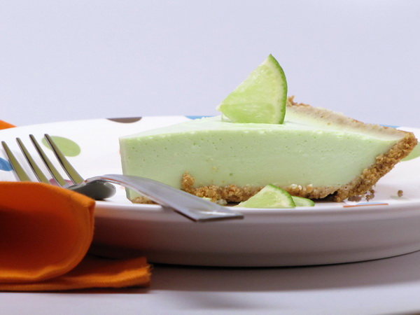 piece of matcha lime pie on a plate with a fork and napkin