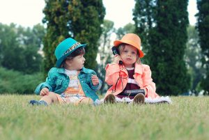 1 boy and 1 girl dress up in neone coloured suits over their clothes little girl looking at the camera on a play phone and little boy looking at her. alldone outside on grass with trees behind