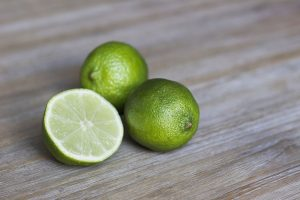 limes on a table with one half cut open