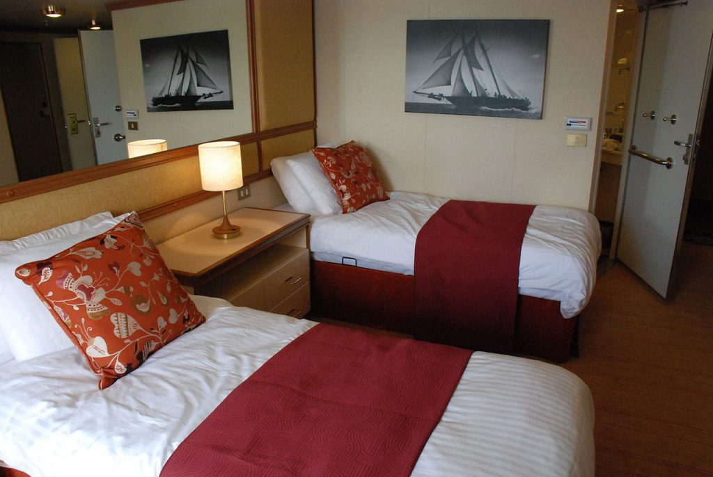 twin beds with white linen and red pillows and throws a lamp in between and a mirror up behind them - it is a cabin on a boat