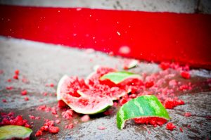 a watermelon smashed on a grey pavement with a red wall behind it