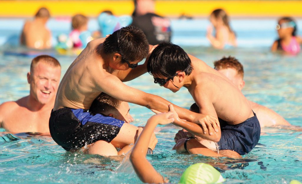two boys on shoulders play wrestling in a pool with others smiling around them