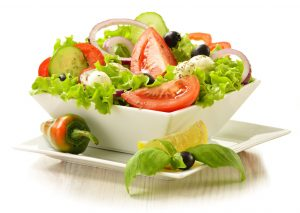 a white square bowl of salad with lettuce, tomato, onion, pepper and olives with a slice of lemon on the side