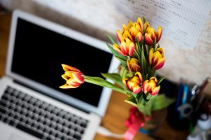 laptop open but off in the background on a desk with a bunch of yellow and red flowers in focus at front of picture. Photo shot from above