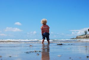 little boy standing with rolled up shorts at the edge of the sea with a small wave in the back ground and clear blue sky. he has blond curly hair
