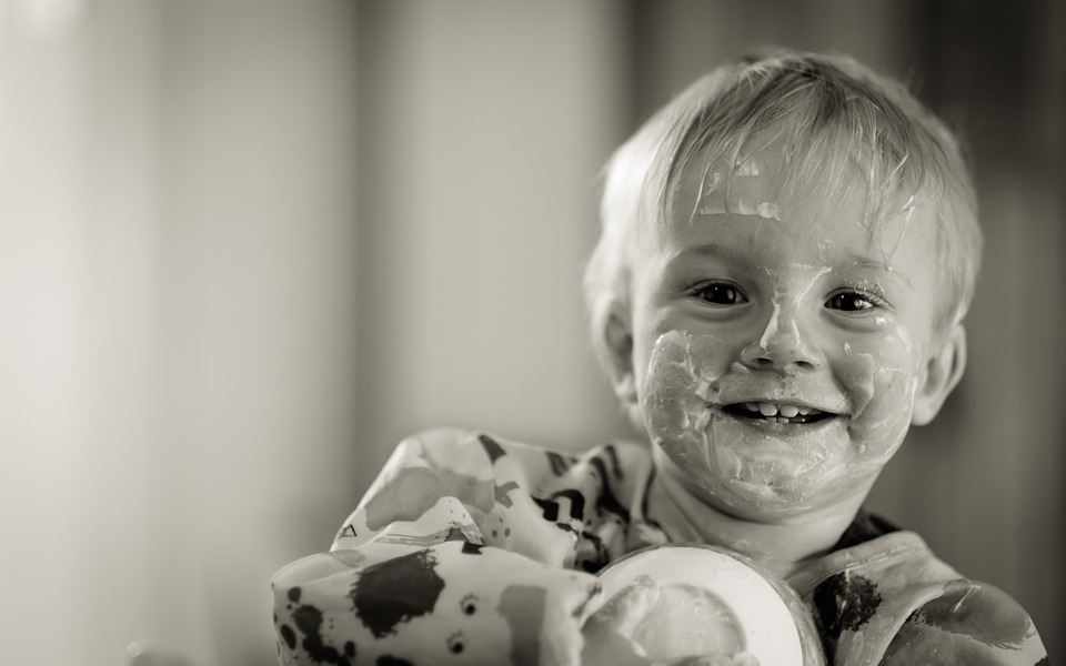 a blond child smiling at the camera with food all over his face. picture in black and white