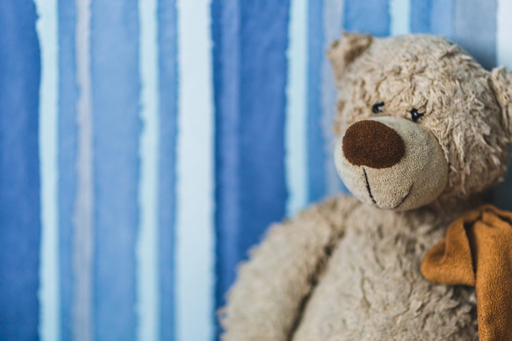 a grey teddy bear against a blue stripe background