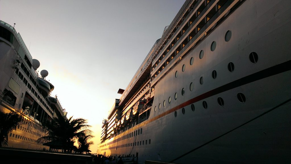 the side of a cruise liner at sunset with a palm tree to the left